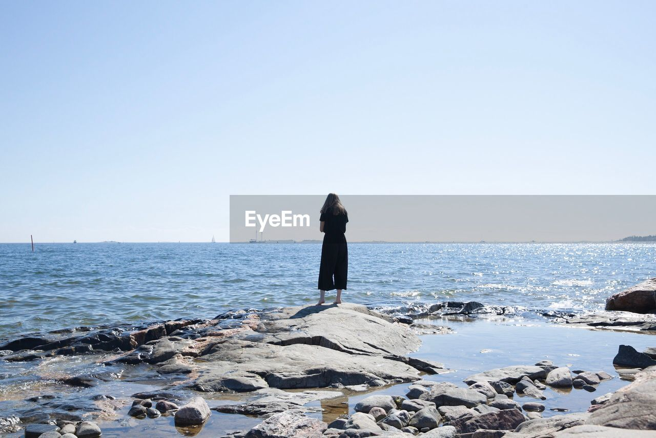 Rear View Of Girl Standing On Rocky Shore Against Clear Sky