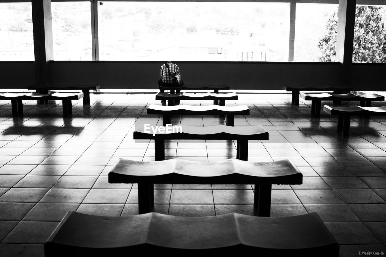 seat, chair, tiled floor, tile, flooring, indoors, table, absence, furniture, no people, empty, day, window, restaurant, education, bench, cafe, classroom, architecture, setting, cafeteria