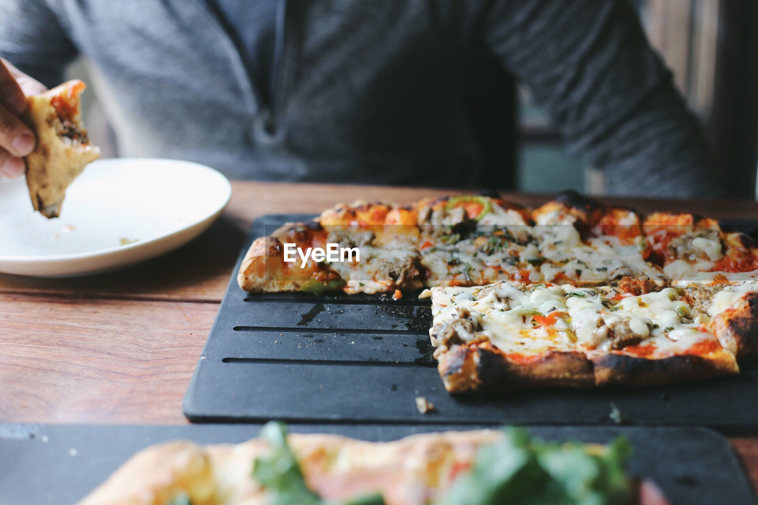 Midsection of man having pizza in restaurant