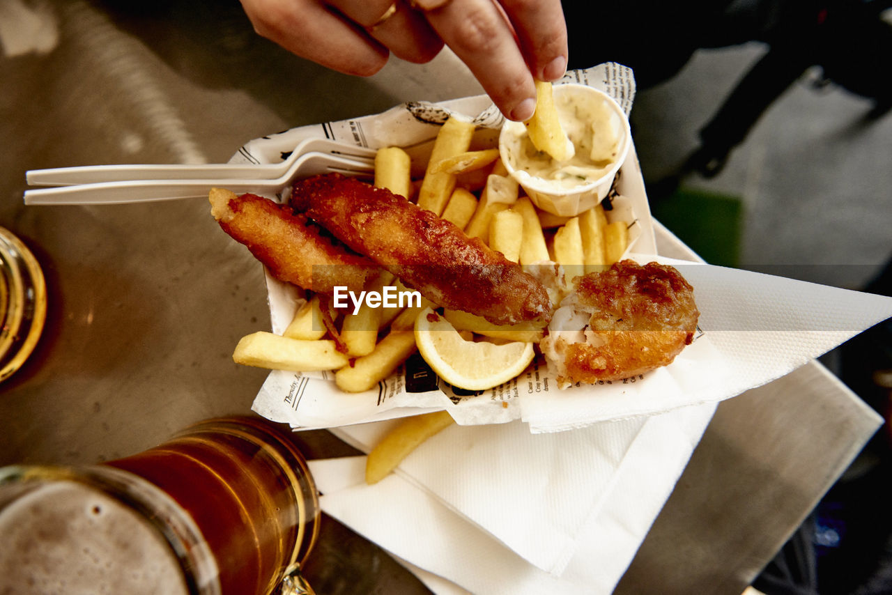 Cropped Image Of Hand Having French Fries And Sausage At Restaurant
