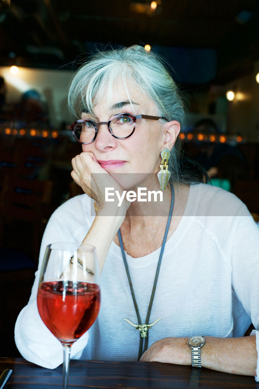 Red wine served on table by thoughtful senior woman