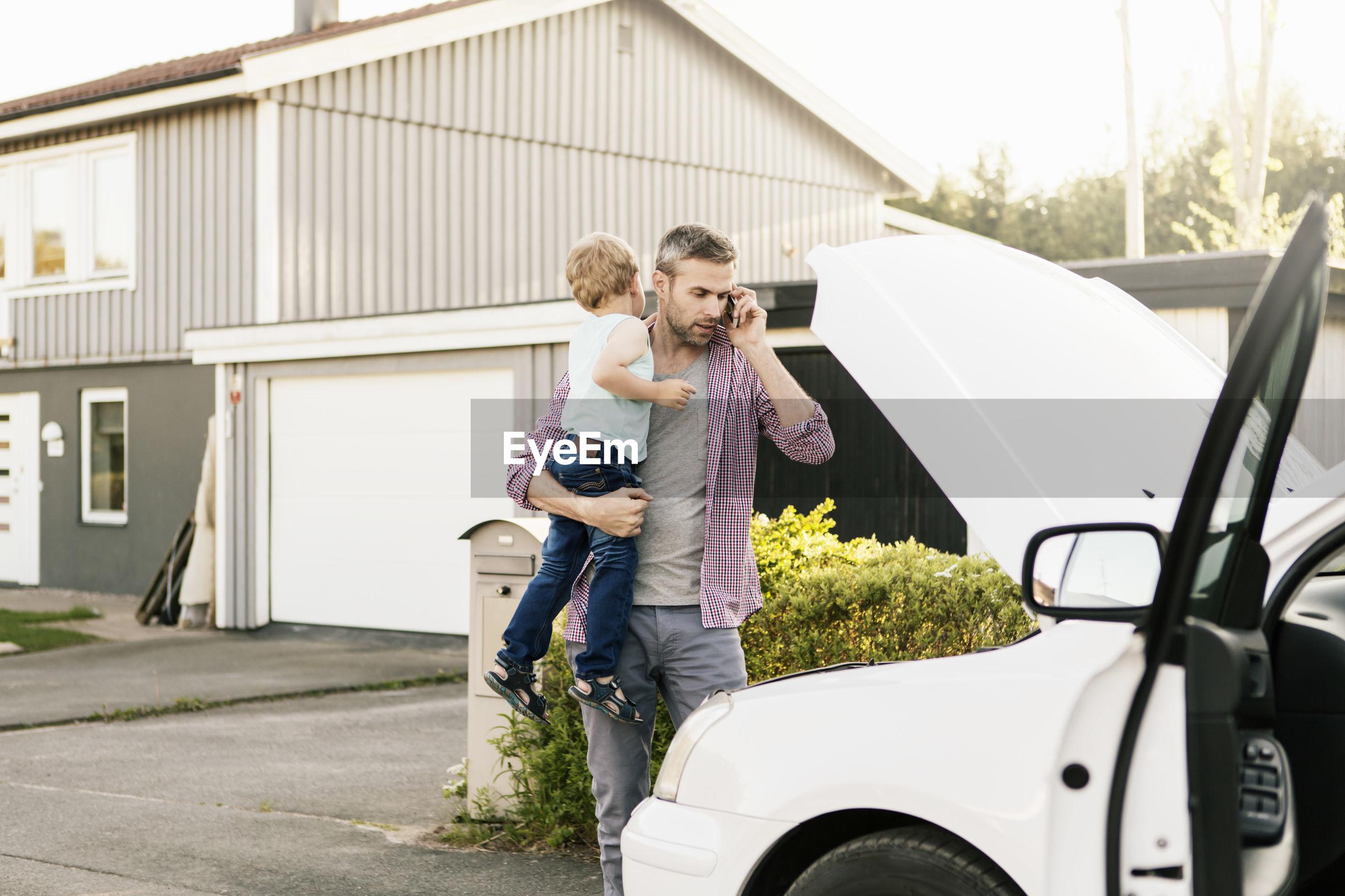 FULL LENGTH OF BOY STANDING BY CAR