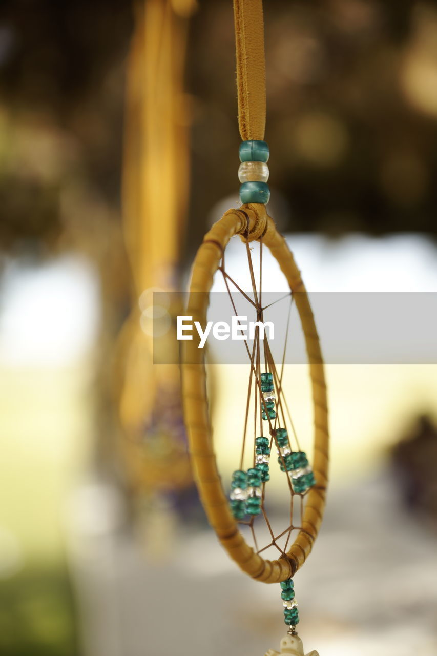 focus on foreground, hanging, close-up, no people, day, jewelry, outdoors, transportation, nature, metal, mode of transportation, rope, shape, craft, single object, art and craft, sunlight, necklace, geometric shape, string, personal accessory