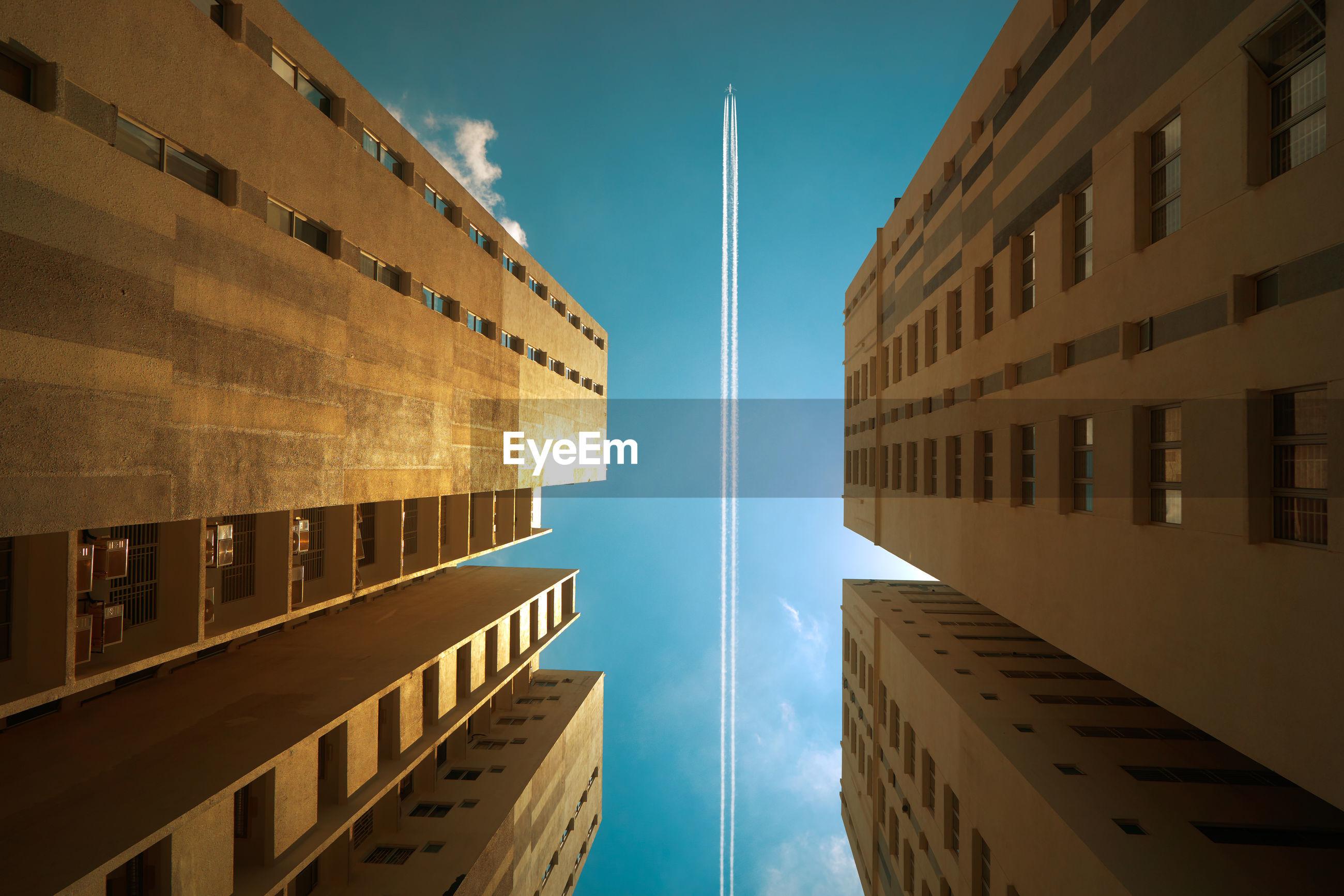 Directly below shot of buildings against blue sky