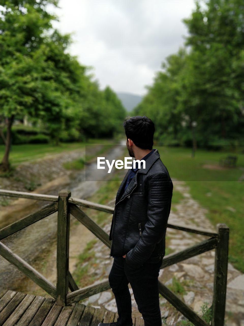 Side view of man wearing black leather jacket standing on footbridge