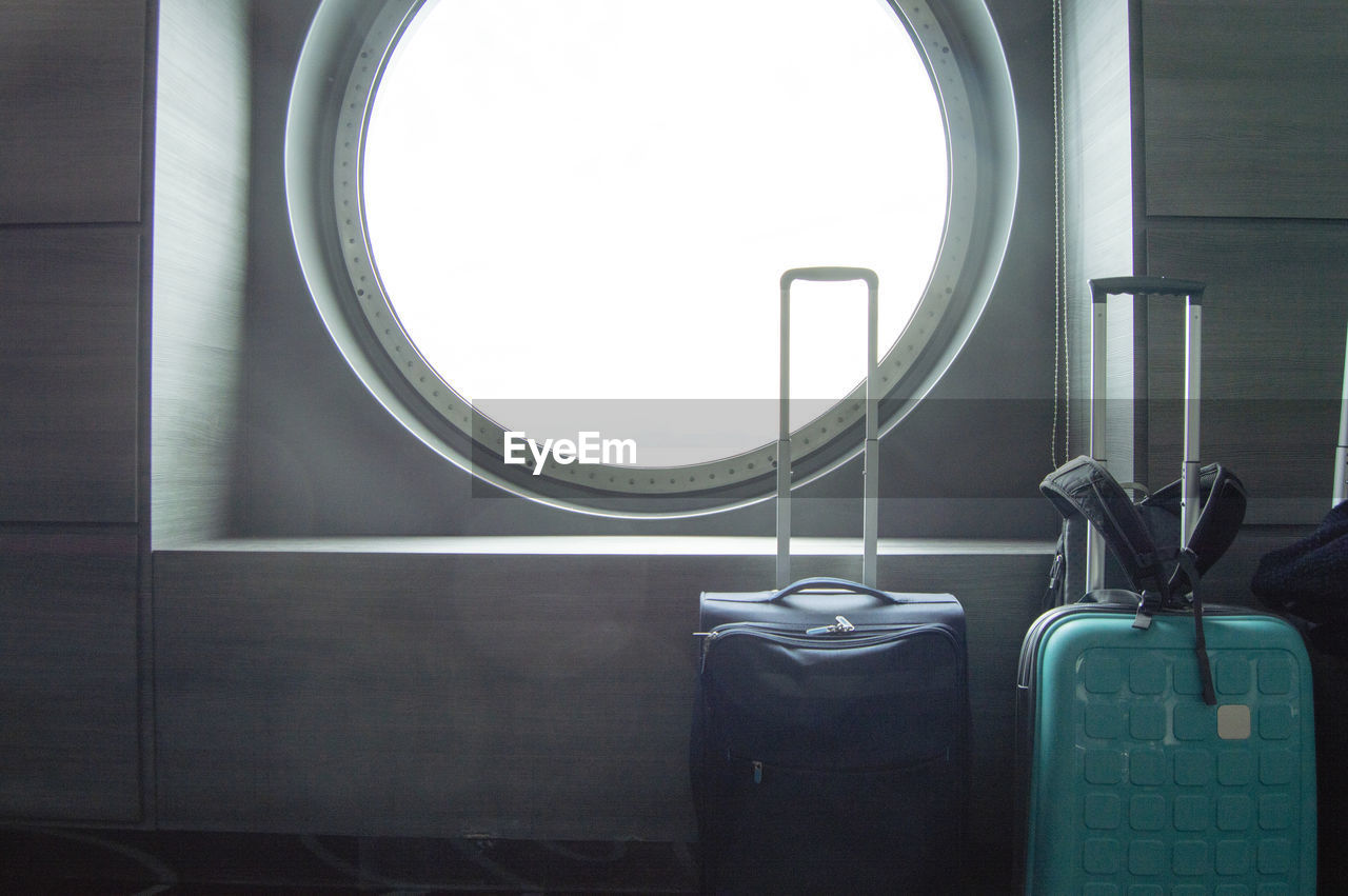Two suitcases for traveling in front of the round porthole of the ship