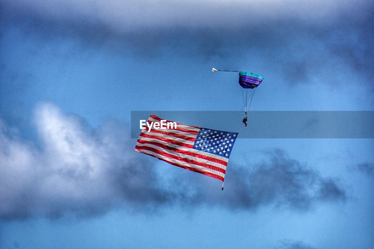 Person Paragliding With American Flag In Sky
