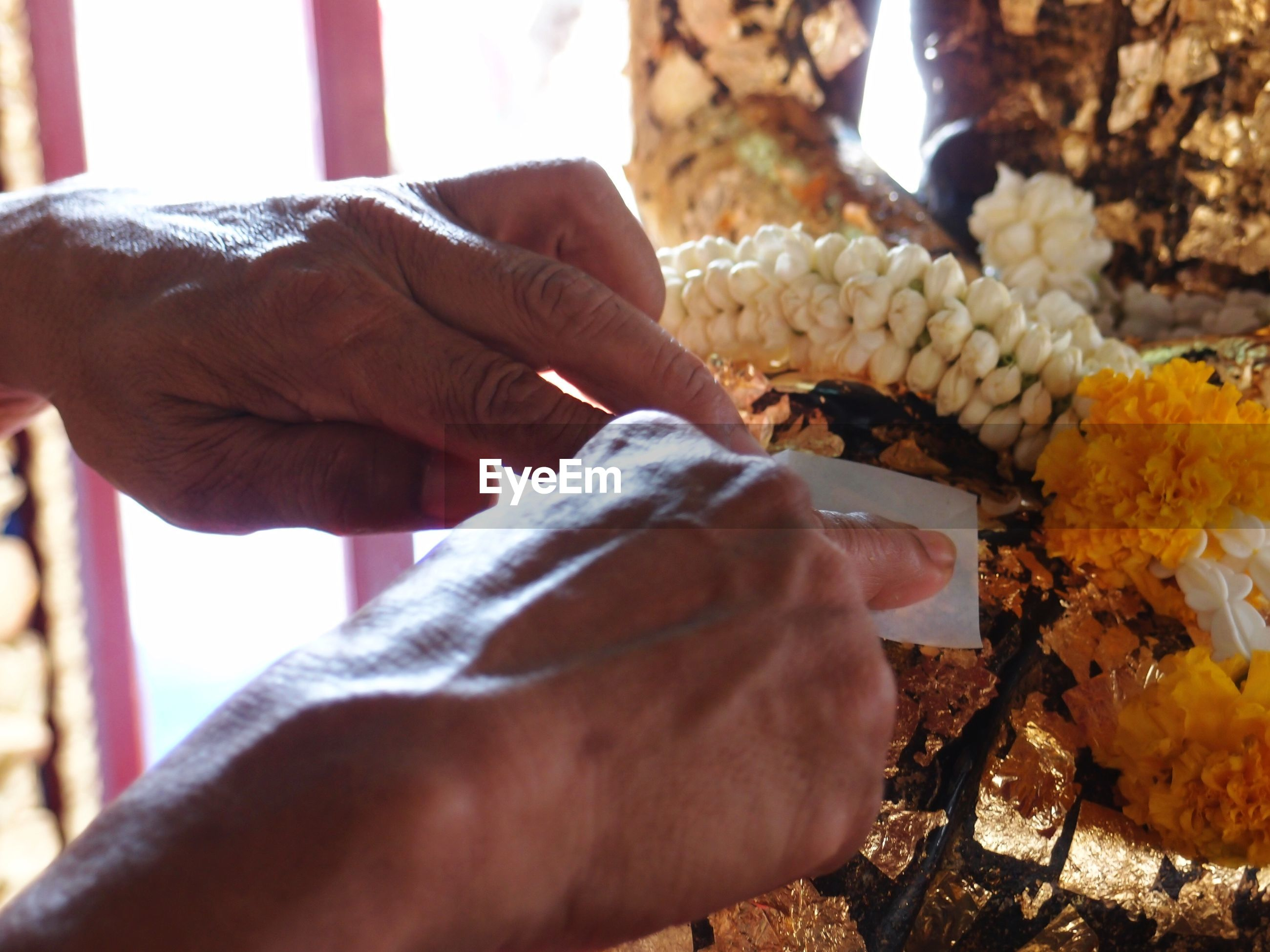 Cropped image of hands performing rituals at buddhist temple