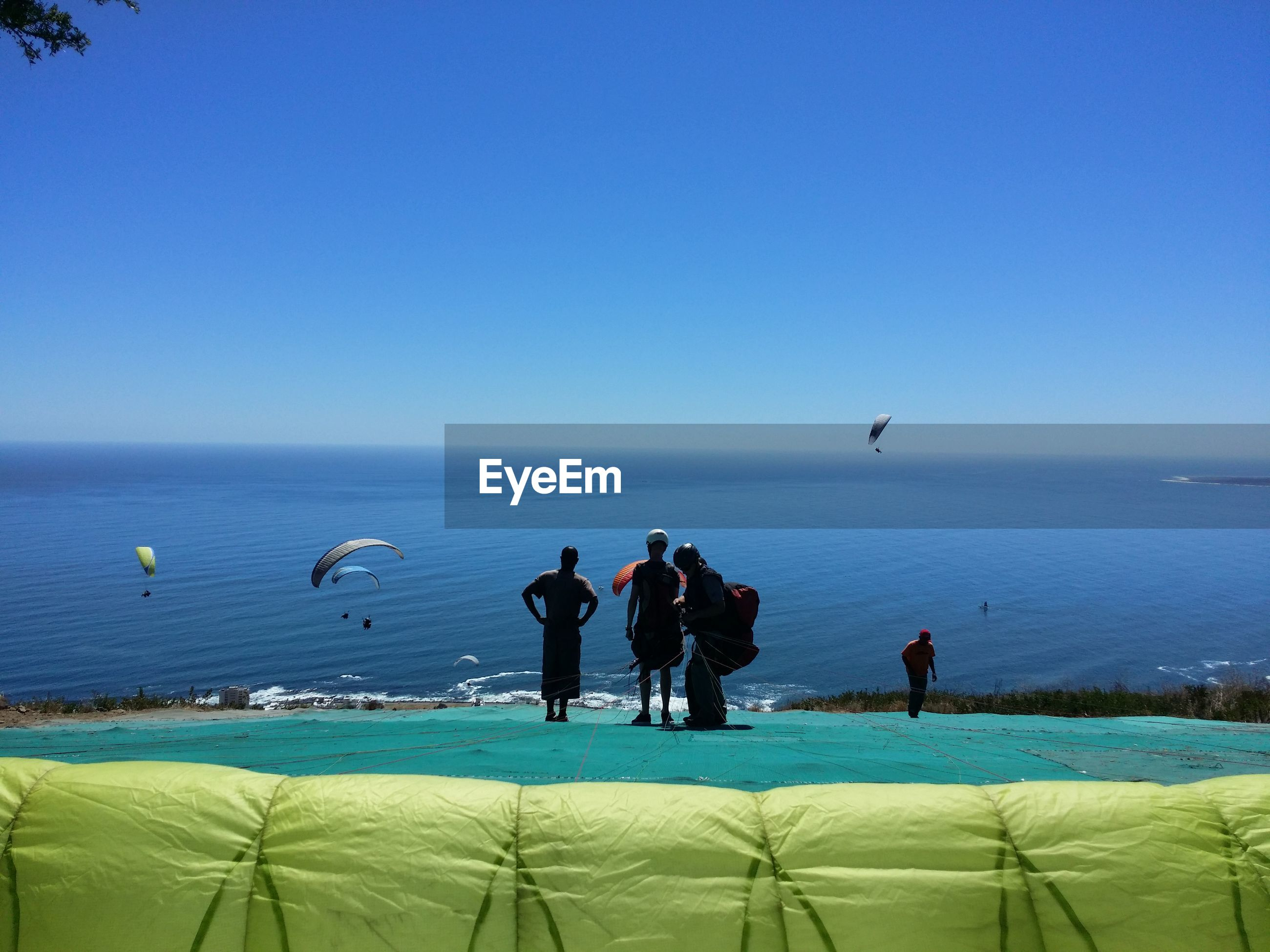 People standing with parachute by sea against clear blue sky