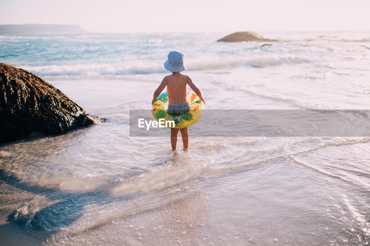 water, sea, beach, land, real people, leisure activity, one person, shirtless, wave, holiday, trip, vacations, sky, lifestyles, standing, full length, nature, beauty in nature, horizon, horizon over water, outdoors