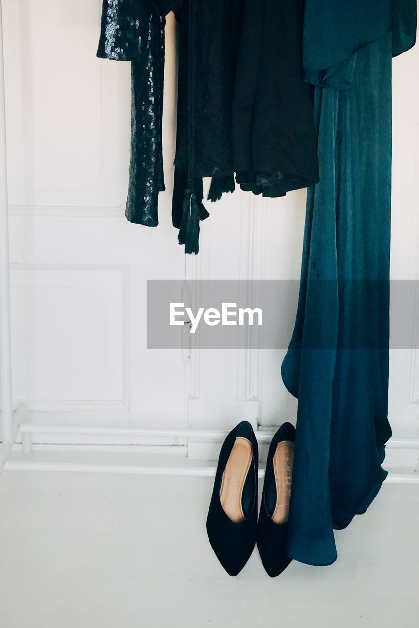 High Angle View Of Black Shoes By White Cabinets At Home