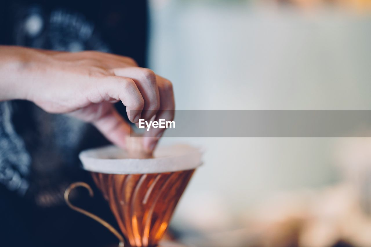 food and drink, hand, real people, human hand, one person, holding, cup, freshness, focus on foreground, preparation, human body part, drink, lifestyles, refreshment, selective focus, indoors, mug, close-up, coffee, preparing food, finger
