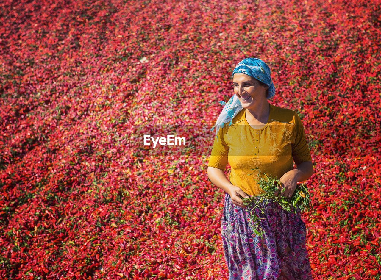 Smiling Woman Standing Against Red Chili Peppers