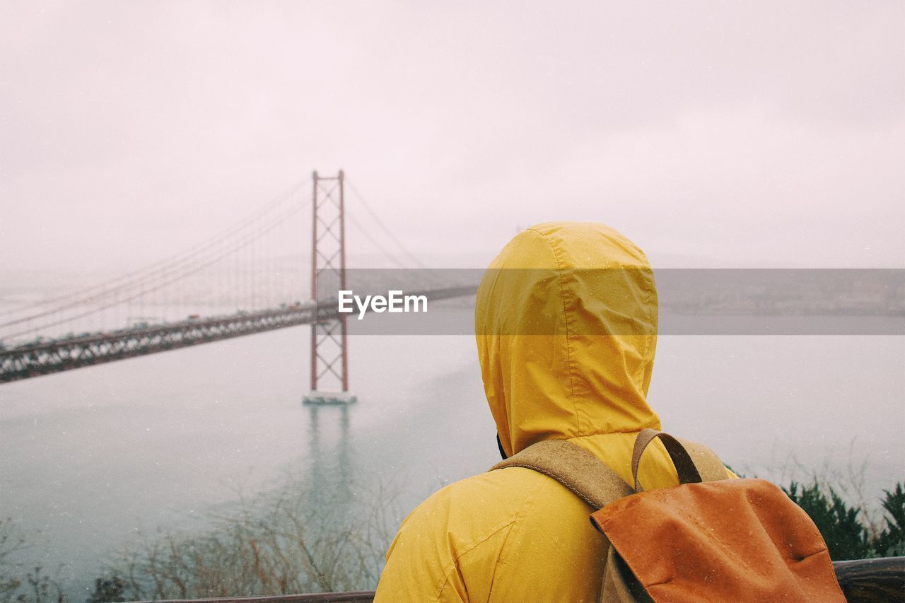 Rear view of young man looking at golden gate bridge over bay against sky