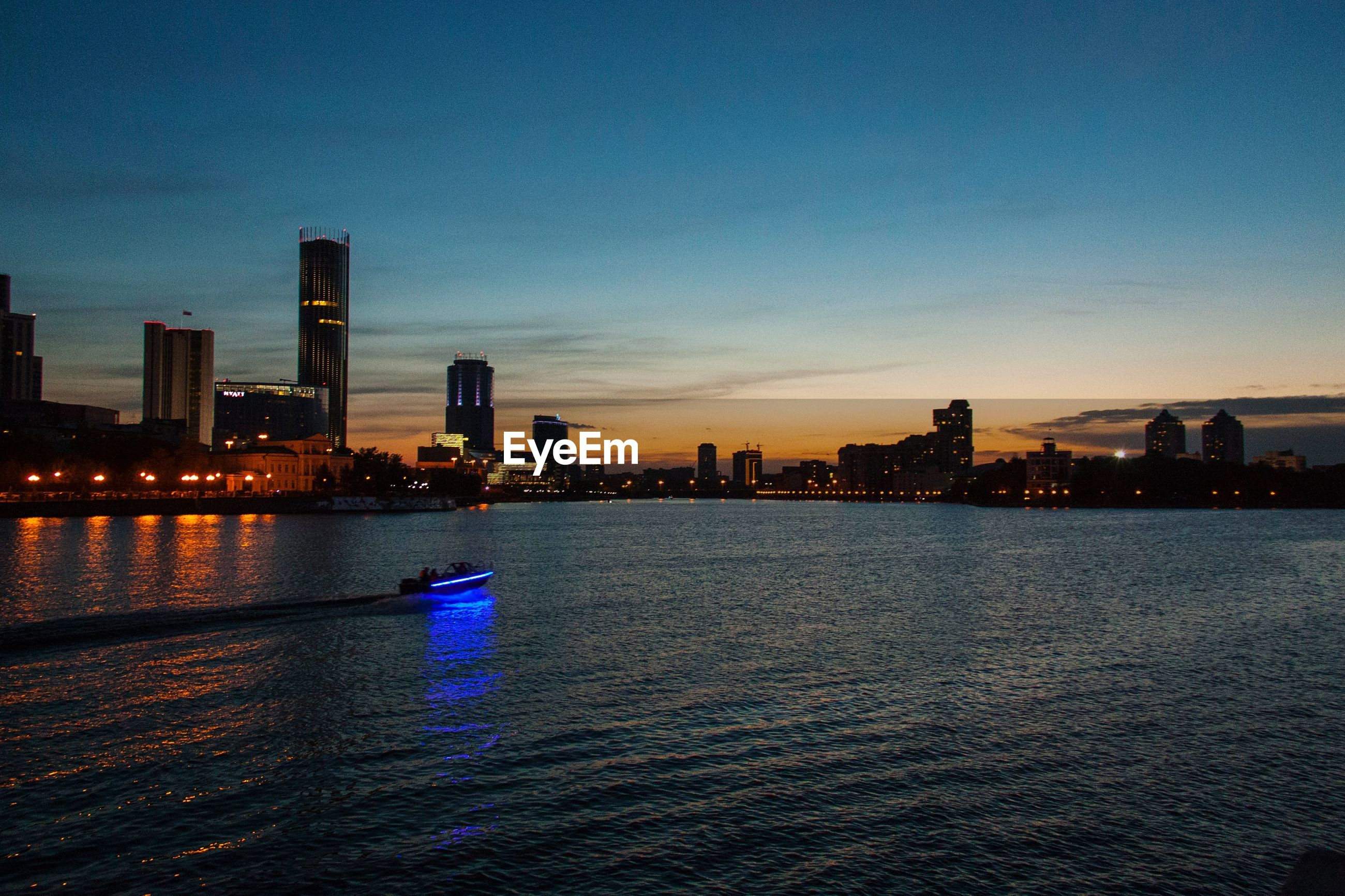 RIVER BY ILLUMINATED CITY BUILDINGS AGAINST SKY AT SUNSET