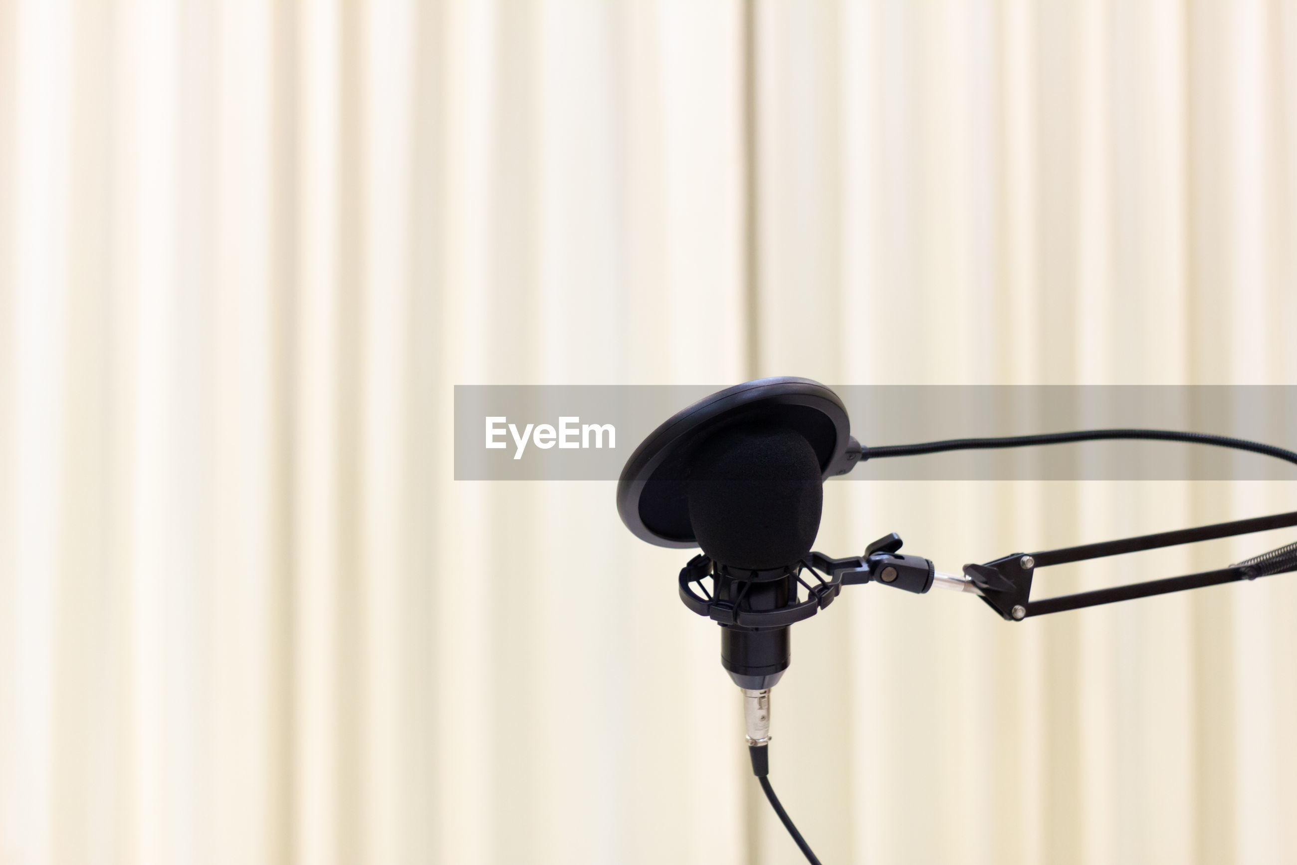 Close-up black microphone with stand and blurred background