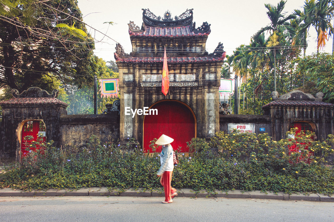 Person In Asian Style Conical Hat Against Traditional Building