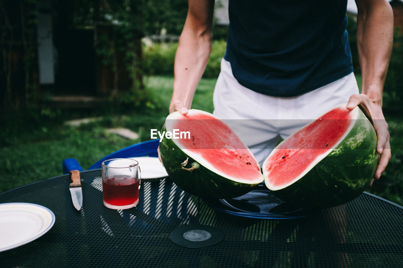 food and drink, freshness, fruit, one person, real people, healthy eating, wellbeing, food, midsection, lifestyles, day, watermelon, focus on foreground, refreshment, table, holding, red, drink, slice, outdoors, preparing food