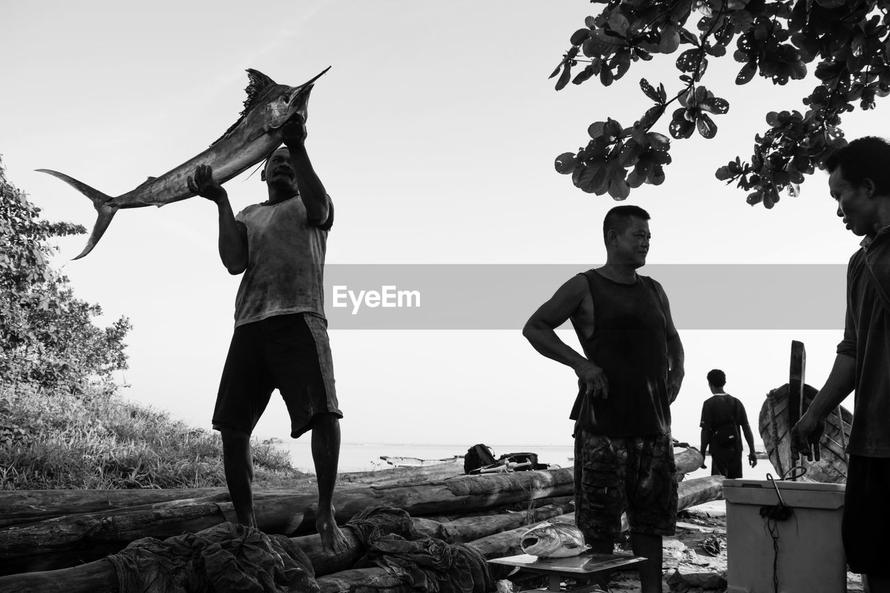 Man With Catch Of Fish Against Clear Sky
