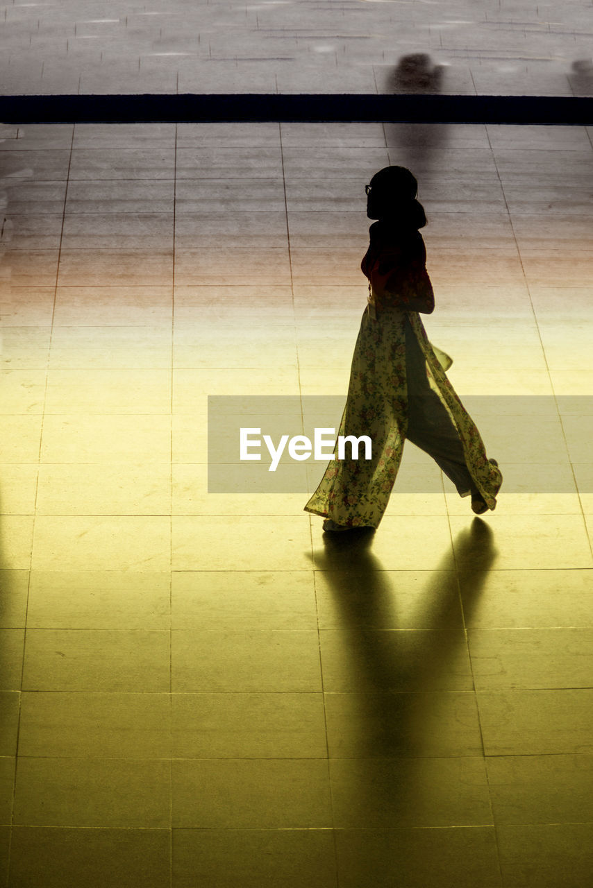 flooring, one person, real people, full length, women, indoors, shadow, tile, lifestyles, tiled floor, walking, standing, leisure activity, day, rear view, high angle view, adult, casual clothing, clothing, hairstyle