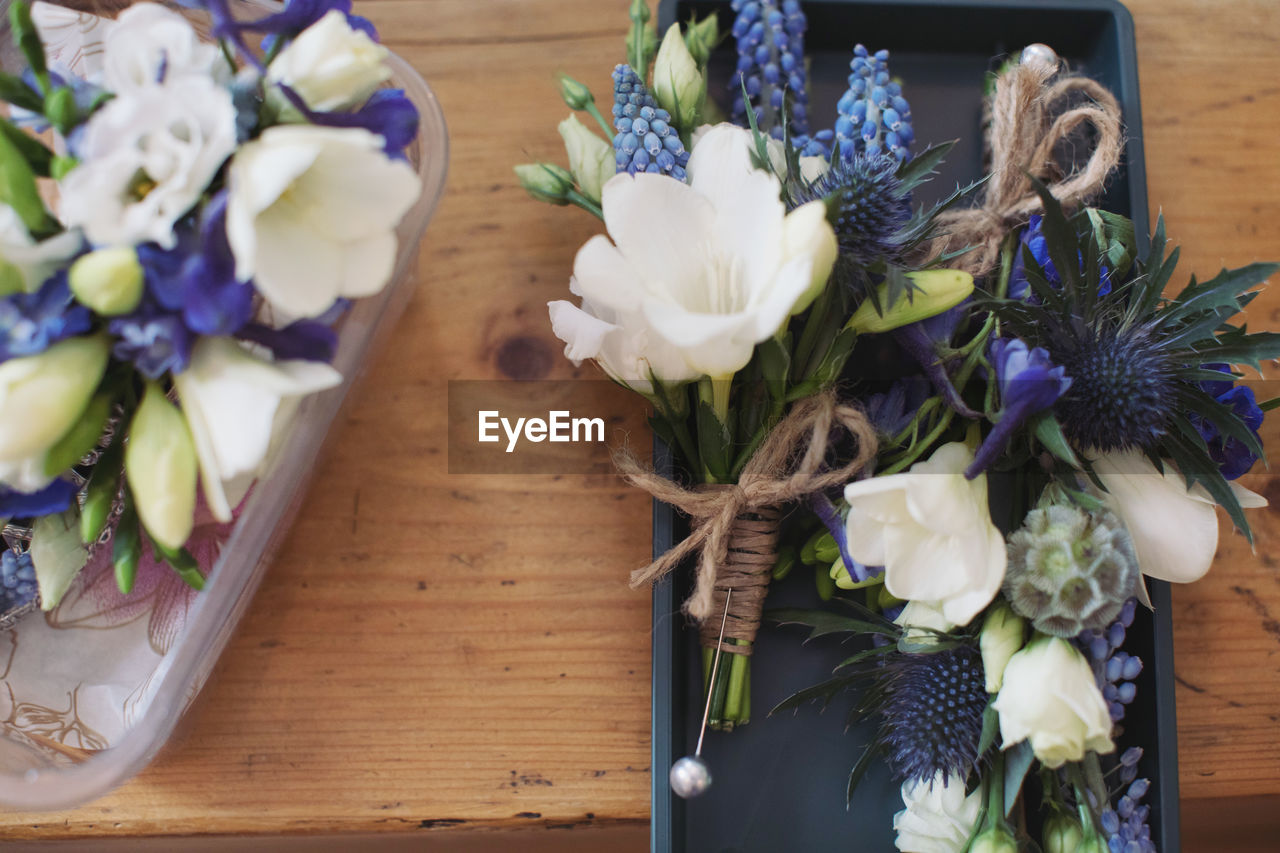 flowering plant, flower, freshness, plant, flower arrangement, table, vulnerability, fragility, indoors, wood - material, beauty in nature, flower head, bouquet, decoration, close-up, inflorescence, petal, nature, no people, still life, purple, bunch of flowers