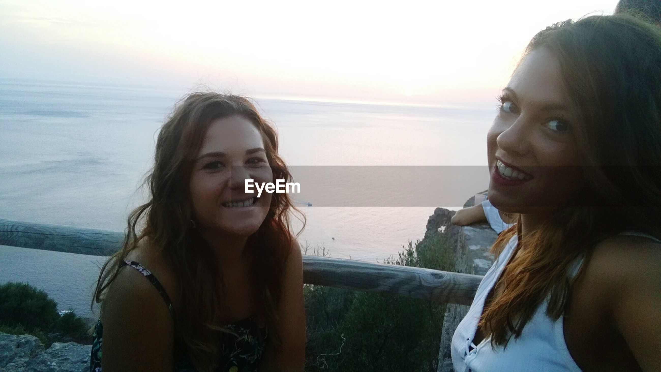sea, water, two people, real people, horizon over water, smiling, nature, togetherness, beach, leisure activity, scenics, young women, young adult, happiness, lifestyles, long hair, outdoors, beauty in nature, love, friendship, vacations, day, sky, bonding, sunset