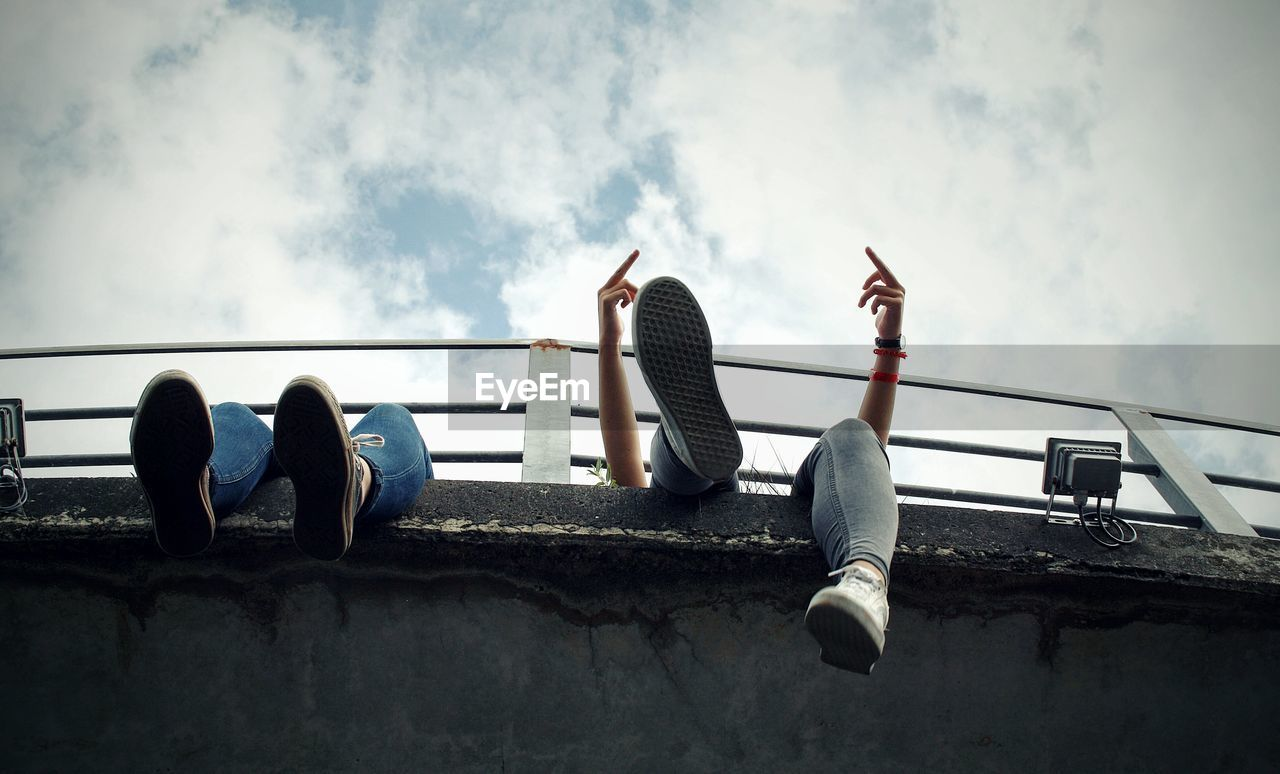 Low section of people sitting on bridge against sky