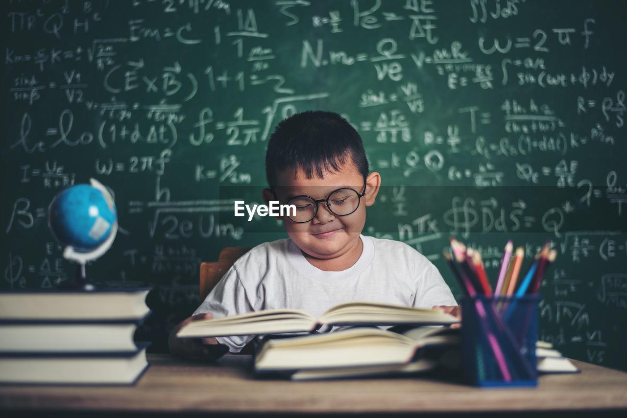 Cute boy wearing eyeglasses against blackboard in classroom