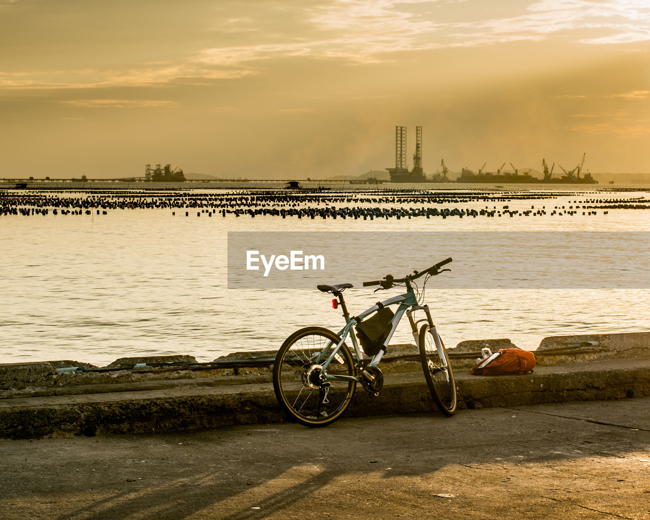 Bicycle parked on beach against cloudy sky