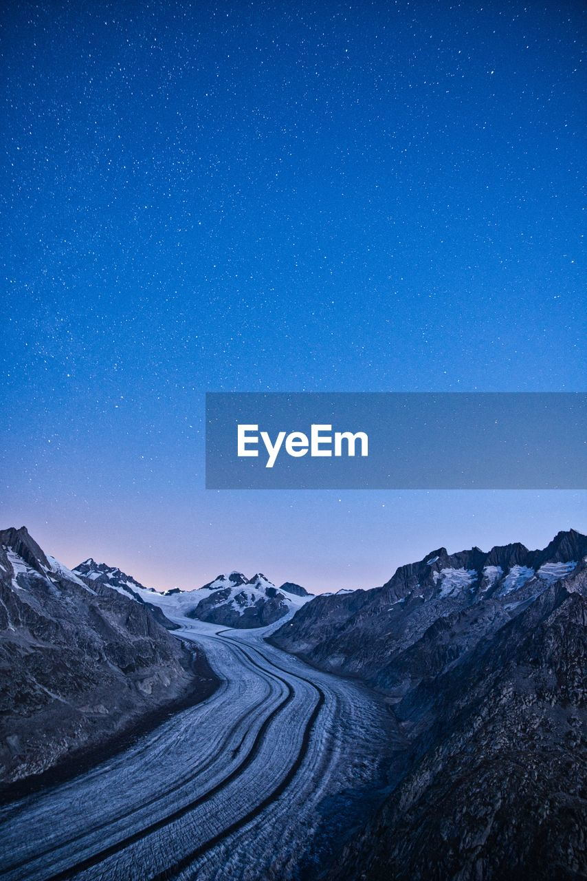 Scenic view of snowcapped glacier against clear blue sky