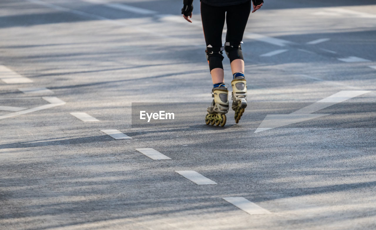 human leg, low section, human body part, body part, road, one person, symbol, sign, real people, transportation, day, shoe, road marking, lifestyles, leisure activity, marking, motion, sport, city, outdoors, human limb, human foot