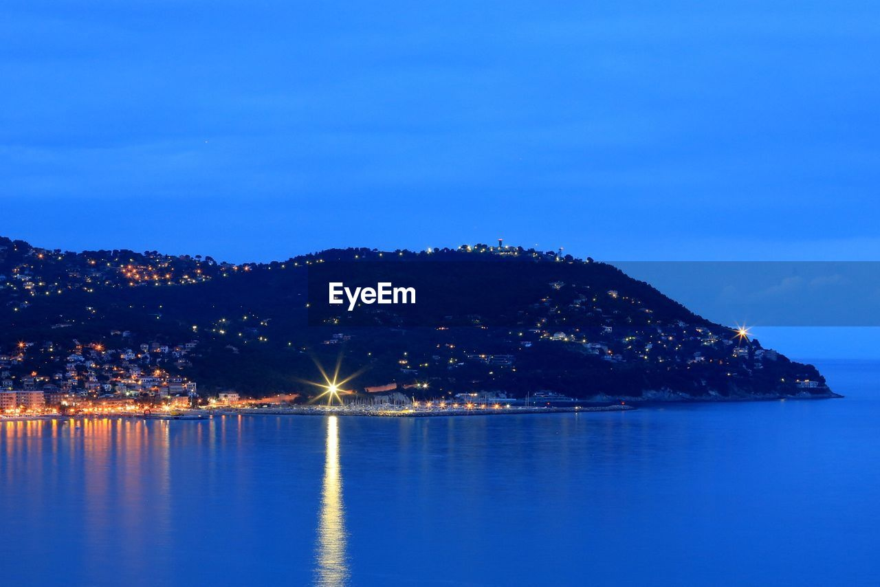 Scenic view of mountain by sea against sky at dusk