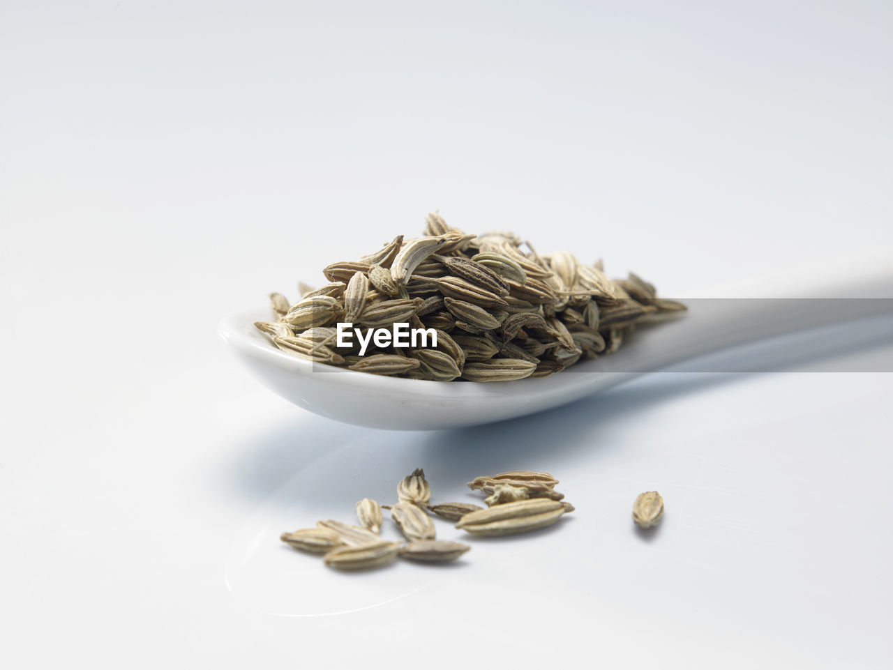 High angle view of cumin seeds in spoon against white background