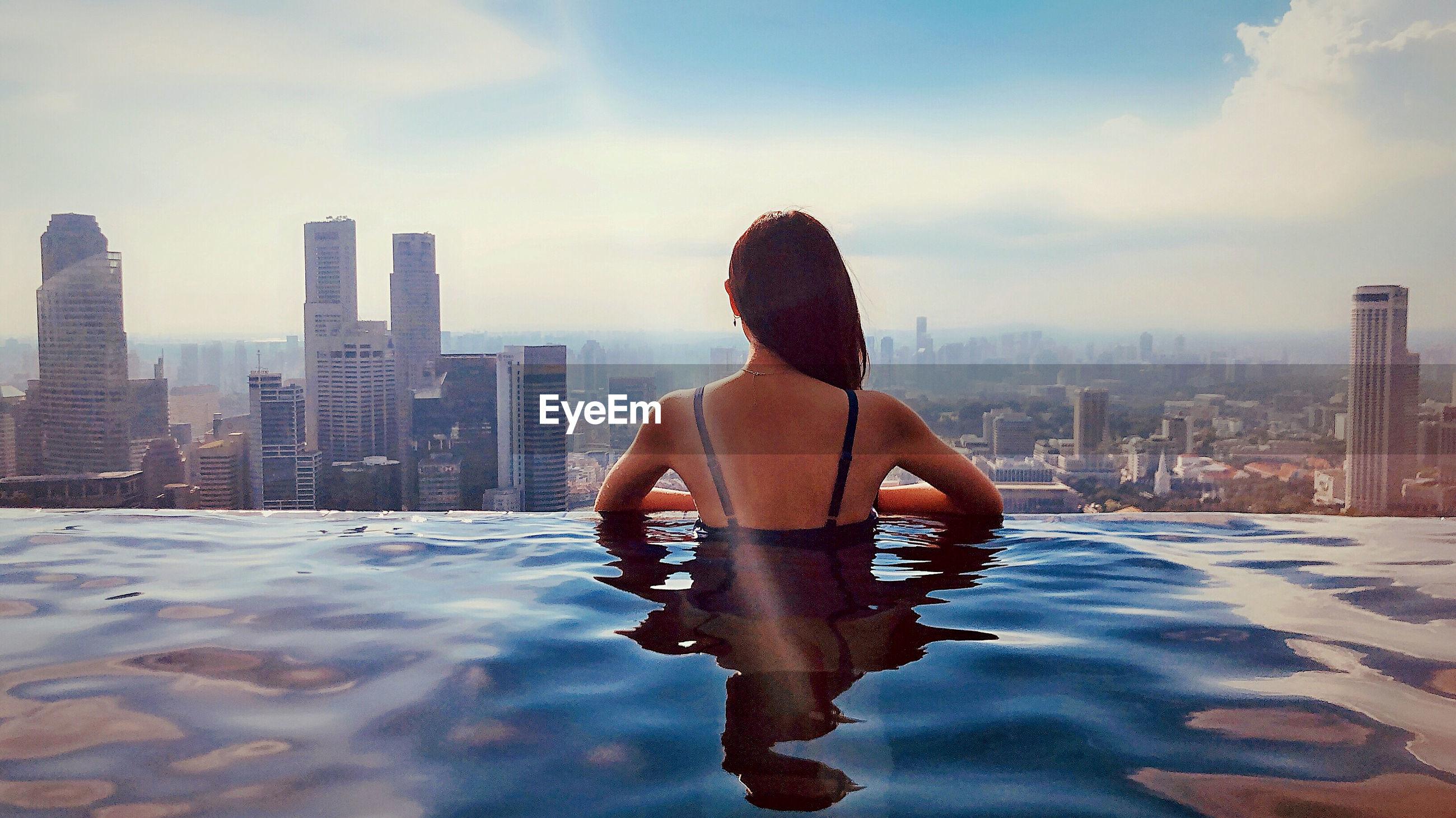 Rear view of woman in infinity pool against buildings in city
