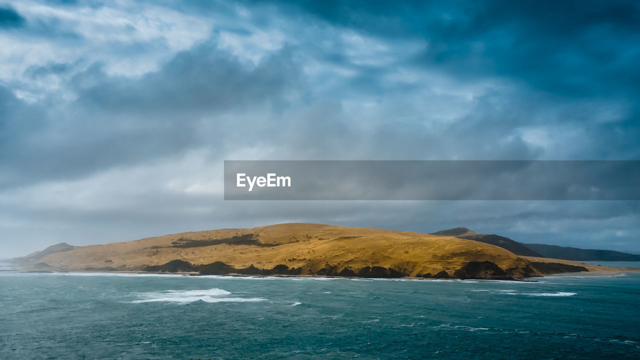 Scenic view of mountain in sea against cloudy sky