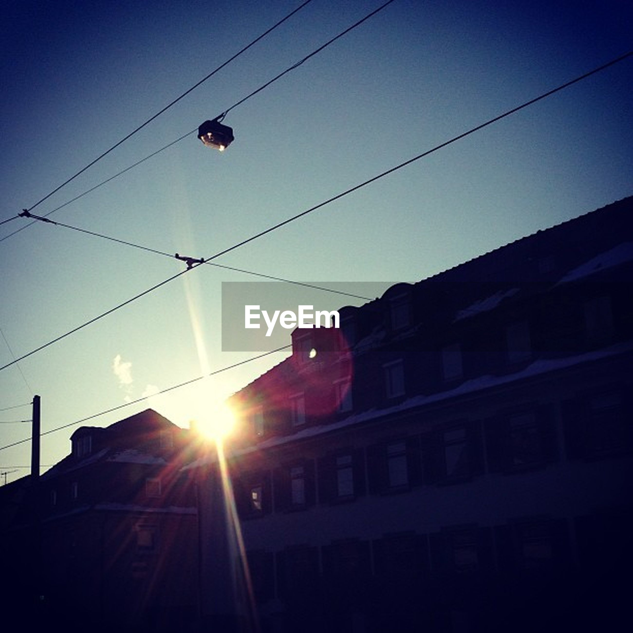 building exterior, architecture, built structure, low angle view, power line, cable, sunset, sky, city, sun, street light, clear sky, transportation, sunlight, building, power cable, silhouette, lighting equipment, city life, outdoors