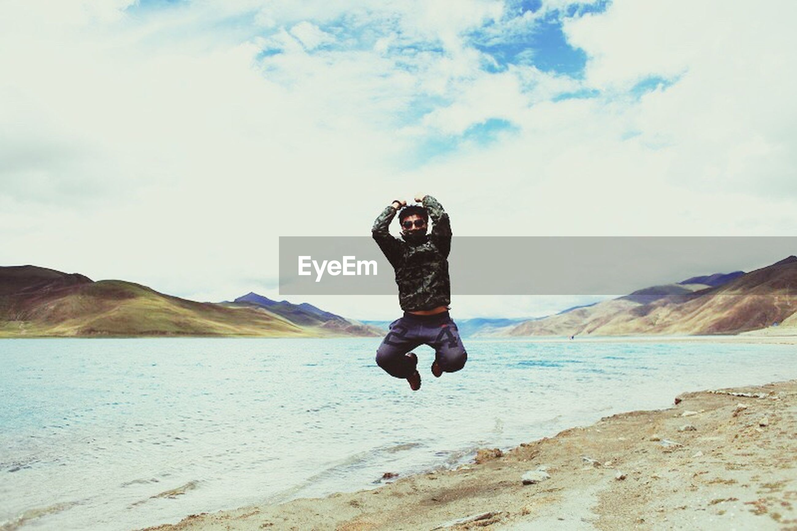 full length, lifestyles, sky, leisure activity, mountain, casual clothing, water, young adult, cloud - sky, standing, sea, tranquil scene, rear view, scenics, tranquility, beach, beauty in nature, nature