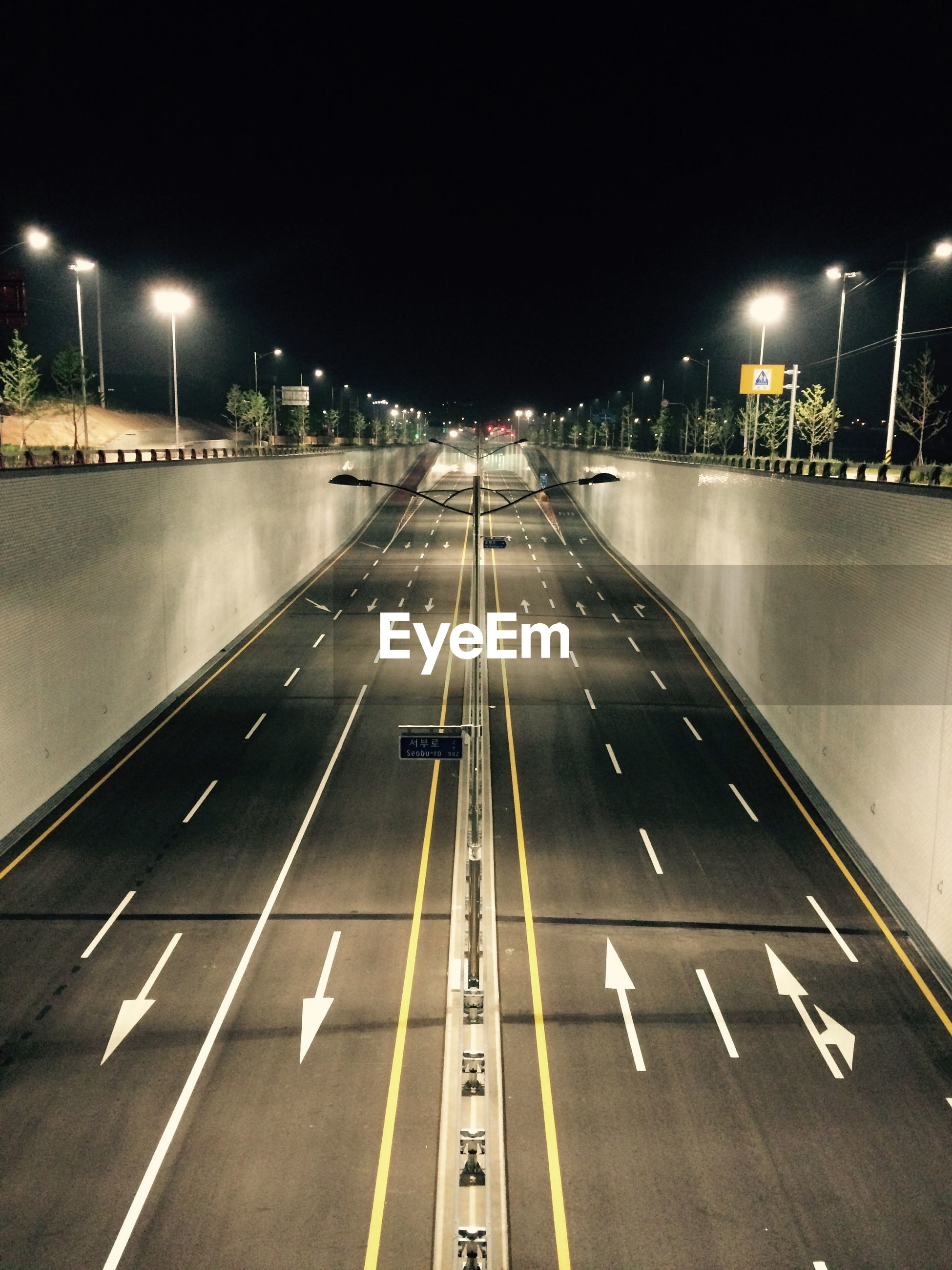 High angle view of empty illuminated road at night