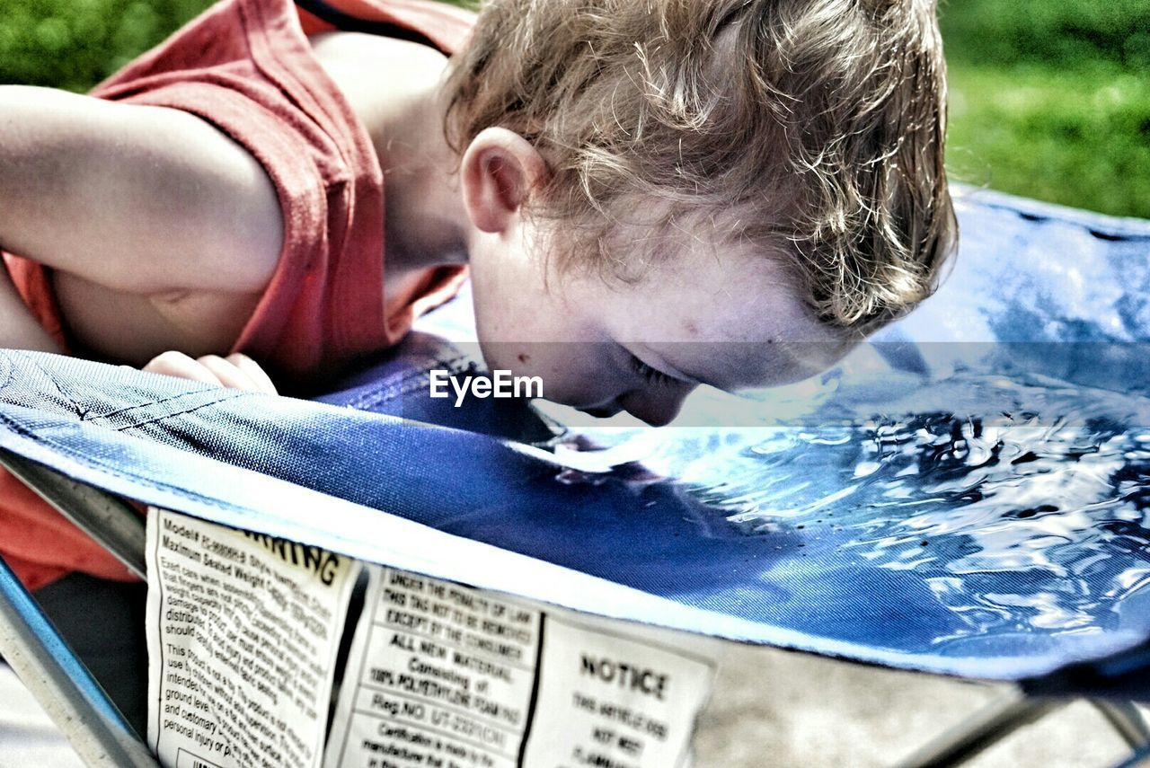 Close-up of toddler drinking water in back yard