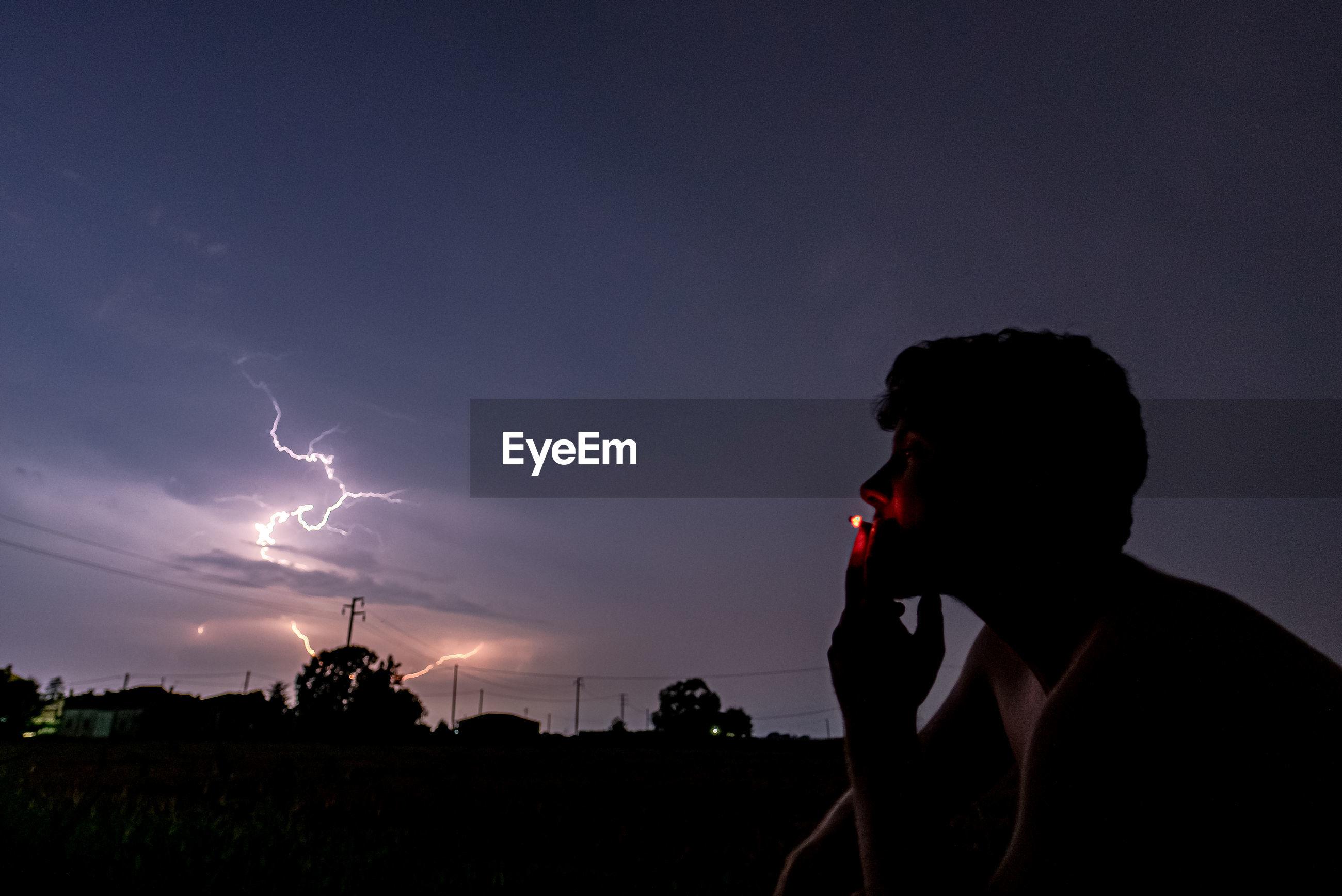 Man smoking cigarette against sky at night