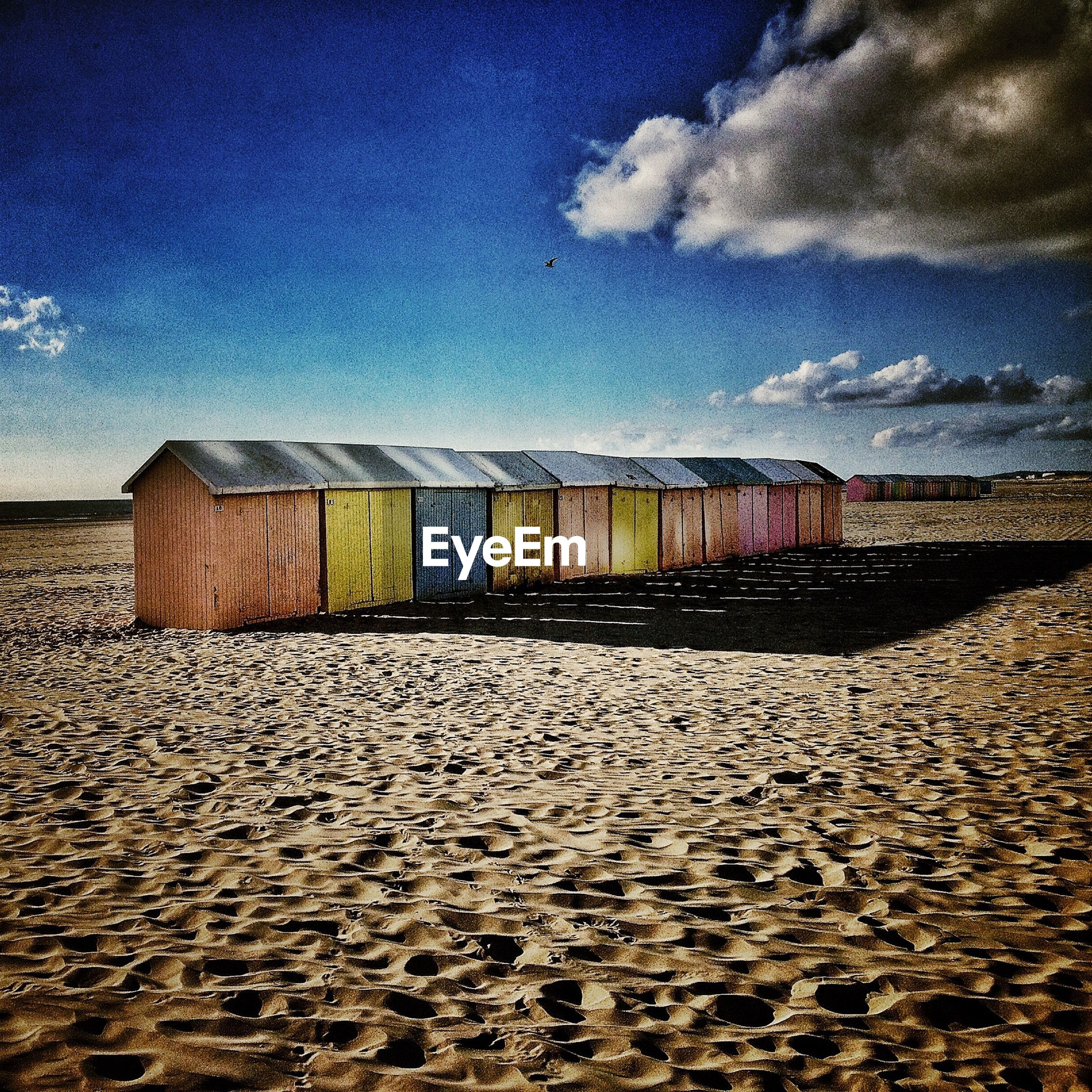 Row of cabins on beach against blue sky