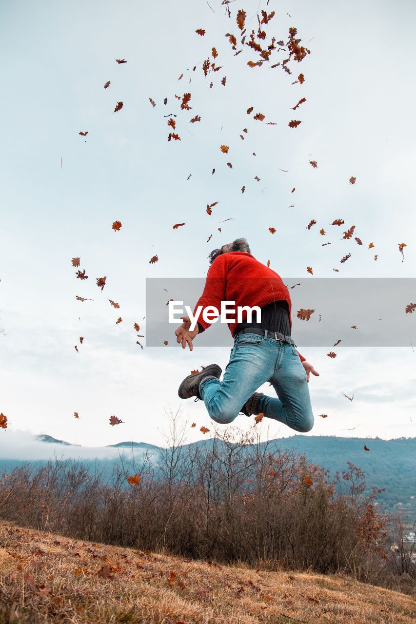 REAR VIEW OF MAN JUMPING ON FIELD