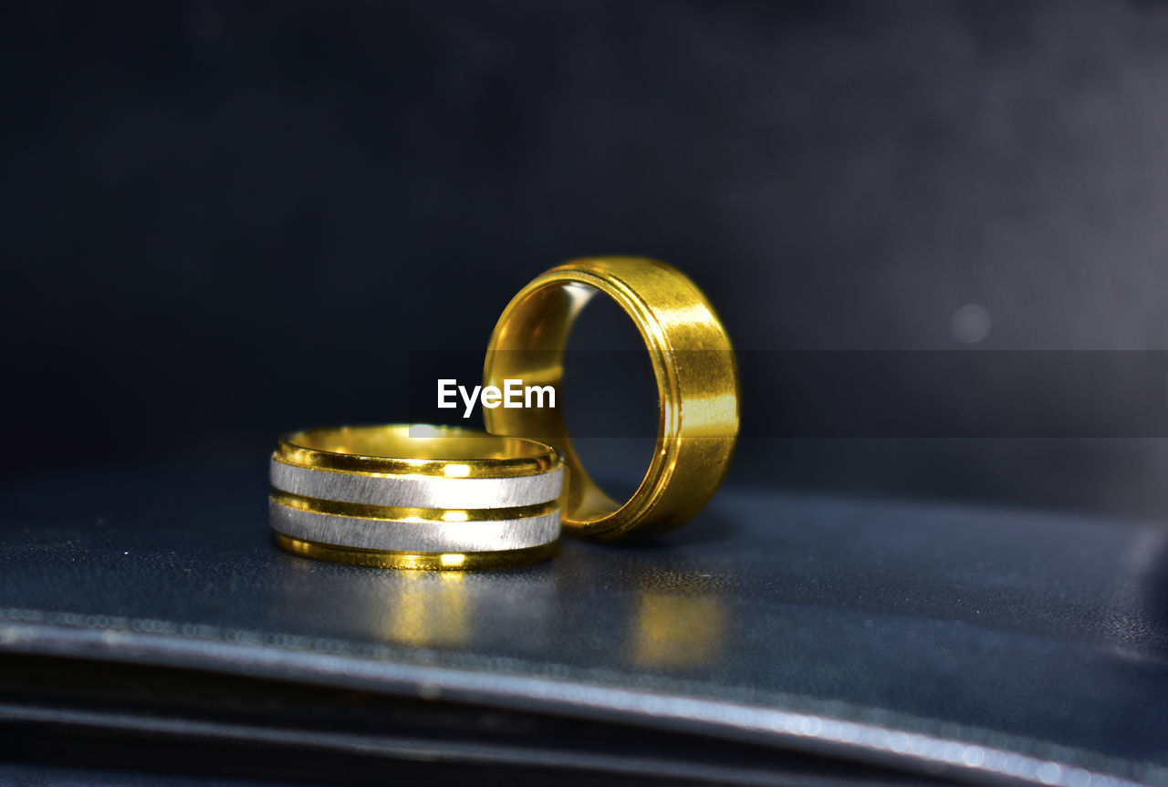 gold colored, metal, gold, close-up, no people, indoors, ring, table, jewelry, still life, shiny, selective focus, wedding ring, wealth, personal accessory, love, wedding, two objects, positive emotion, life events, luxury