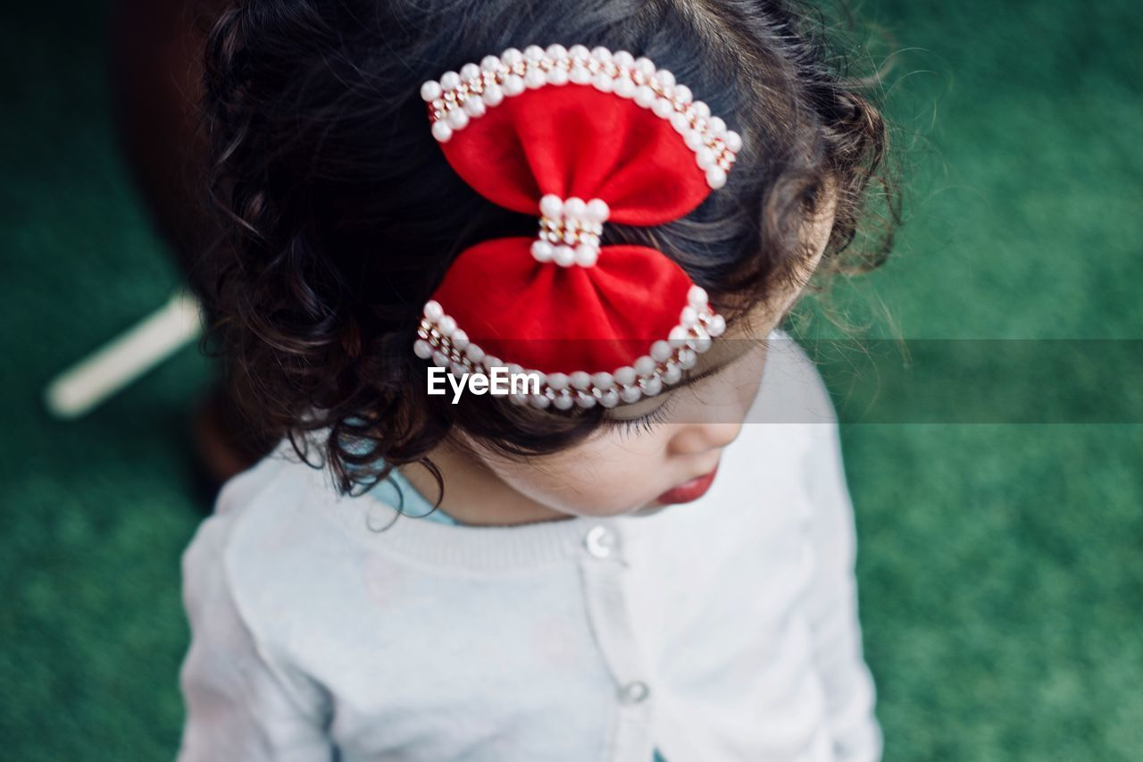 High Angle View Of Girl Wearing Red Bow On Black Hair