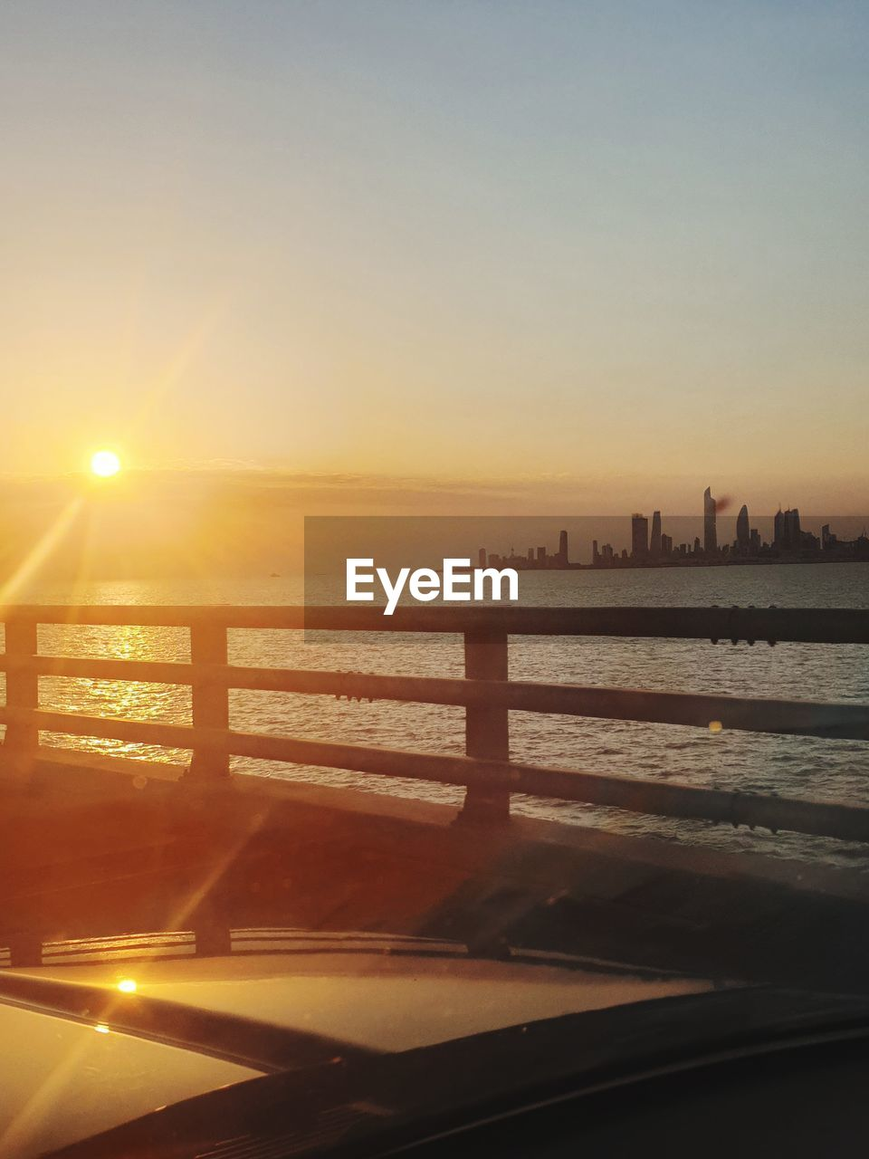 sky, water, architecture, sunset, built structure, nature, sunlight, building exterior, no people, sun, city, scenics - nature, beauty in nature, railing, clear sky, sea, outdoors, reflection, orange color, lens flare, bright, skyscraper