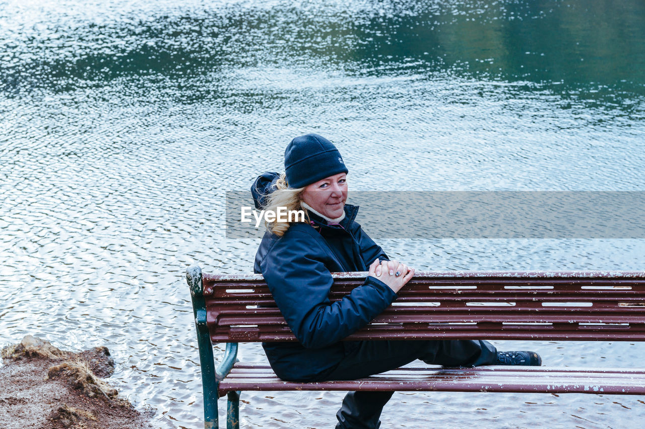 sitting, one person, leisure activity, water, bench, young adult, lifestyles, real people, full length, seat, clothing, nature, winter, casual clothing, day, young women, lake, warm clothing, outdoors