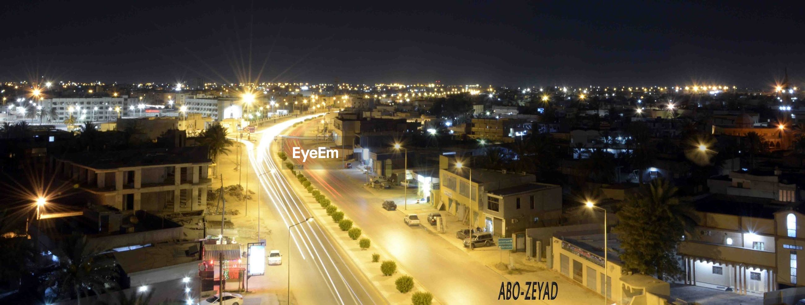 illuminated, night, city, building exterior, cityscape, architecture, high angle view, built structure, residential district, city life, residential building, road, street, residential structure, transportation, crowded, street light, sky, lighting equipment, light trail