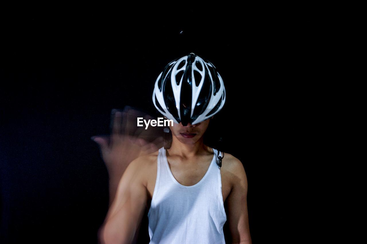 Man Wearing Sports Helmet Against Black Background