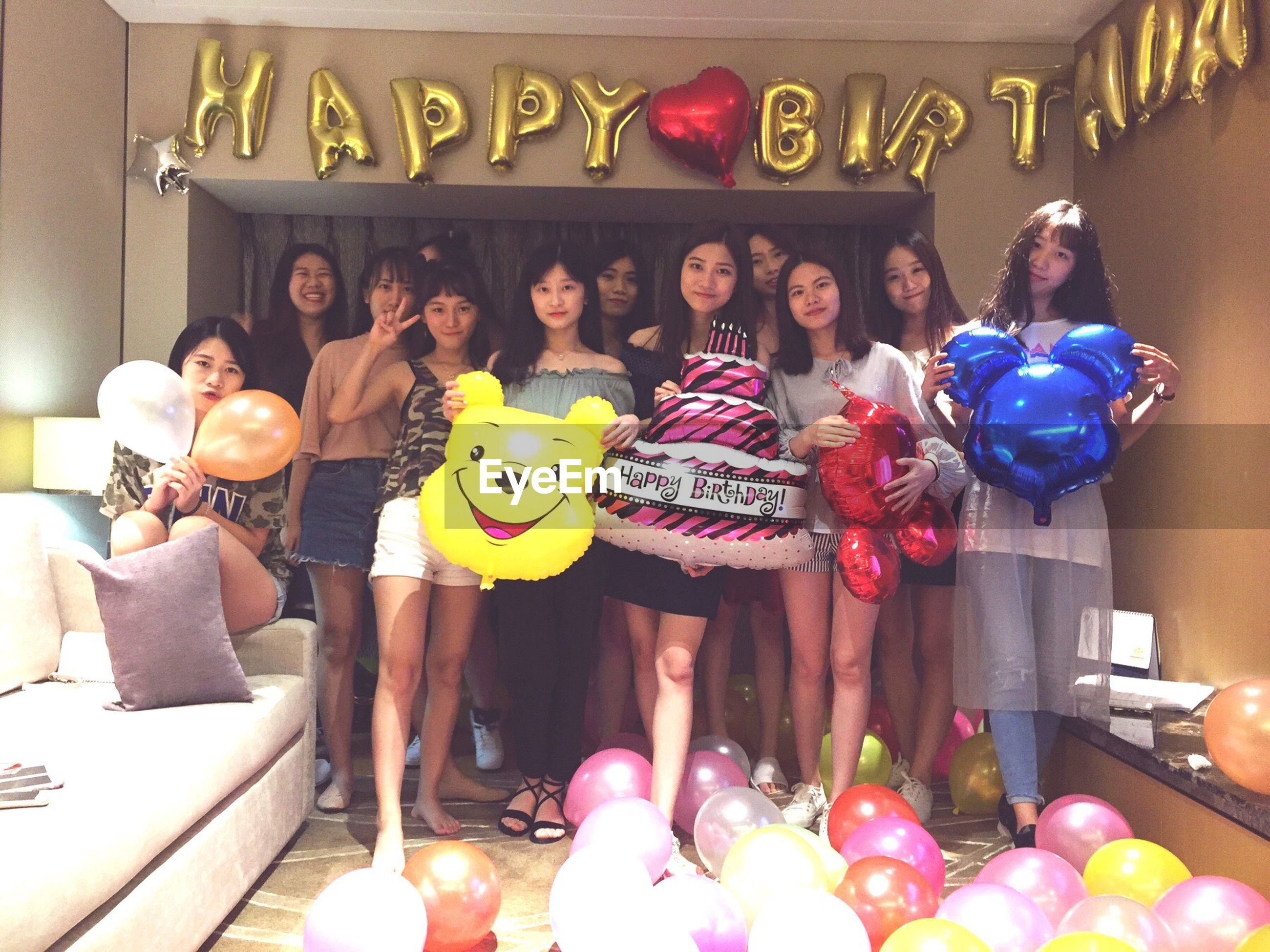 real people, front view, full length, lifestyles, indoors, standing, leisure activity, looking at camera, balloon, portrait, large group of people, celebration, togetherness, friendship, young adult, young women, day, smiling, happiness, people