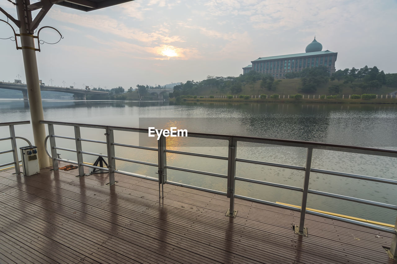 Pier Over River Against Sky During Sunset In City